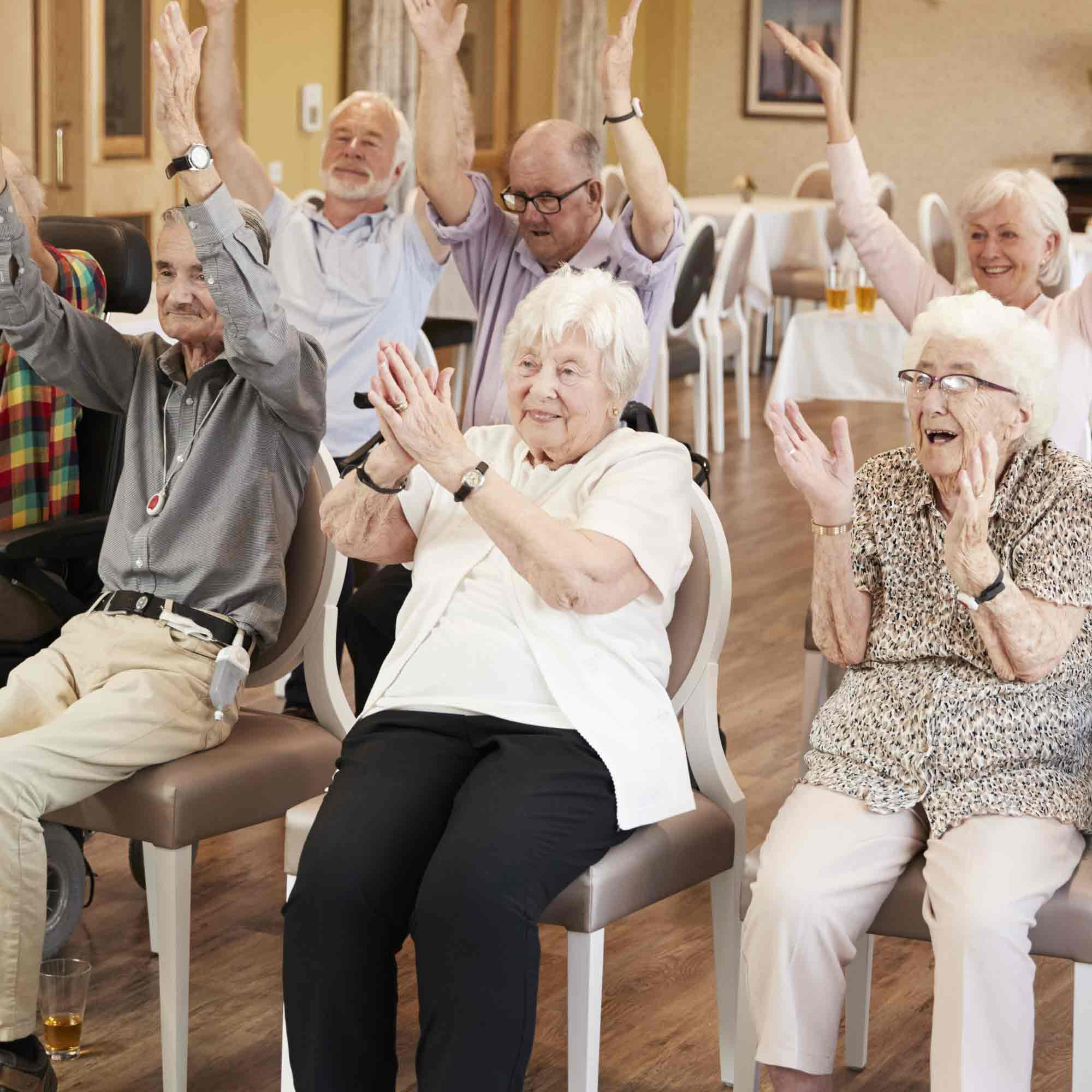 Senior citizens sitting, clapping and holding their hands in the air in a large room.