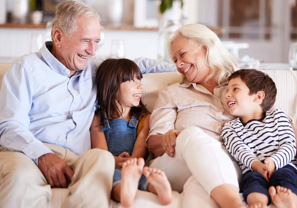 Grandparents sitting on a white sofa with a boy and a girl laughing