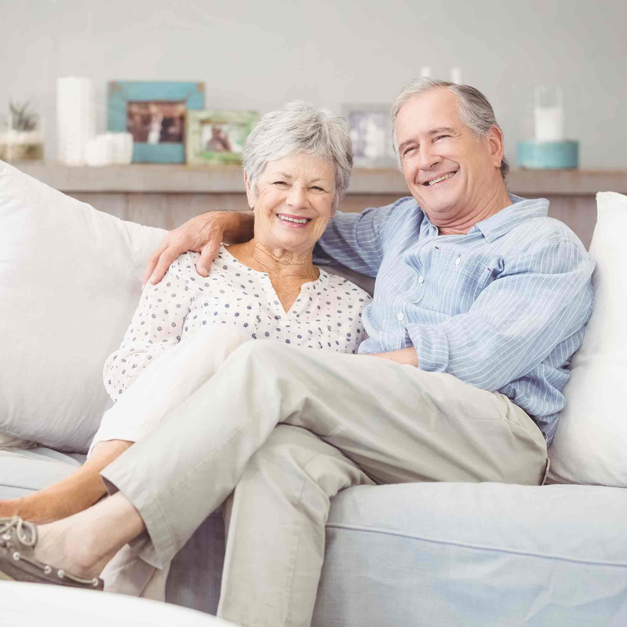 Senior couple sitting on a white sofa with picture frames in the background