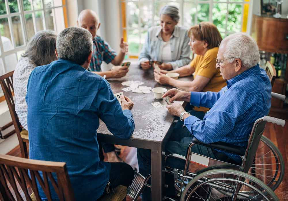 A group of senior citizens, one in a wheel chair, sitting at a table playing cards.