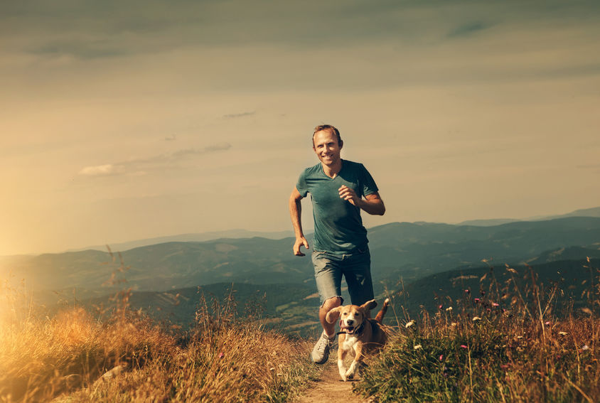 Man jogging through a field with a dog in the mountains.