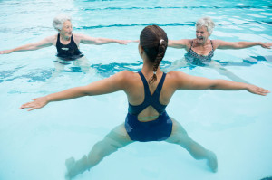 75906042 - smiling female trainer with senior women exercising in swimming pool