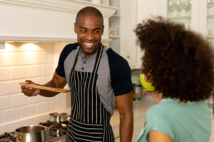 Front view of a mixed race couple standing in the kitchen, the man smiling and offering the woman a taste of food from a wooden spoon